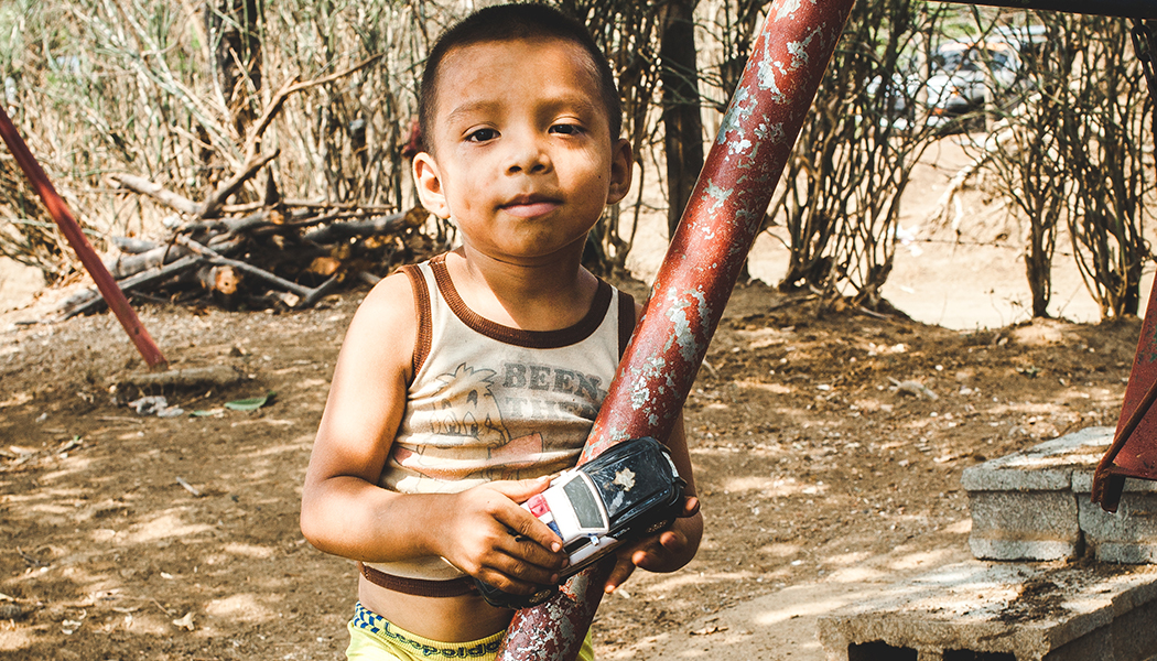 Azael Amparo plays with his toy car near his home.