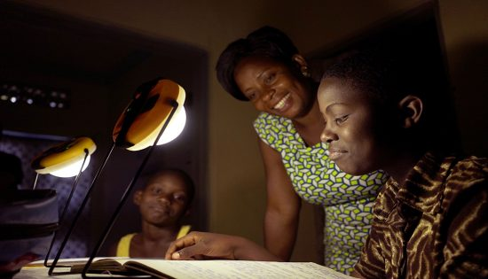 Student studying at night thanks to solar lamps