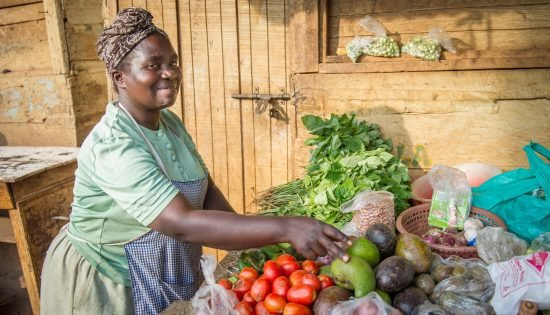 FINCA Client with Her Produce Table