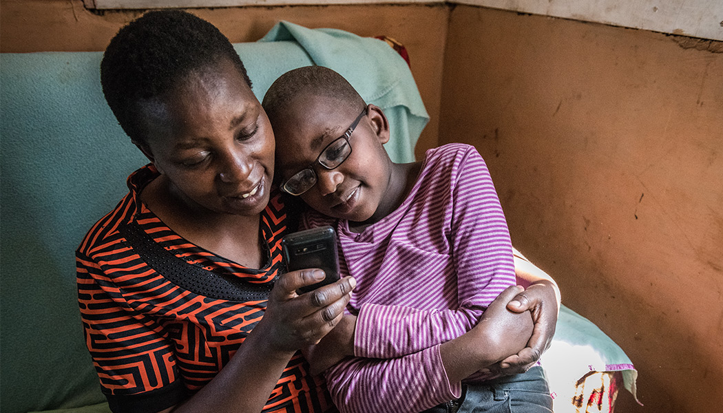 A-Mother-Helping-her-Child-on-Eneza-Educations-Mobile-Learning-Platform