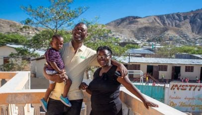 Annesse Aristild and Kerlande Toussaint and their youngest child in front of their school in Gonaives, Haiti