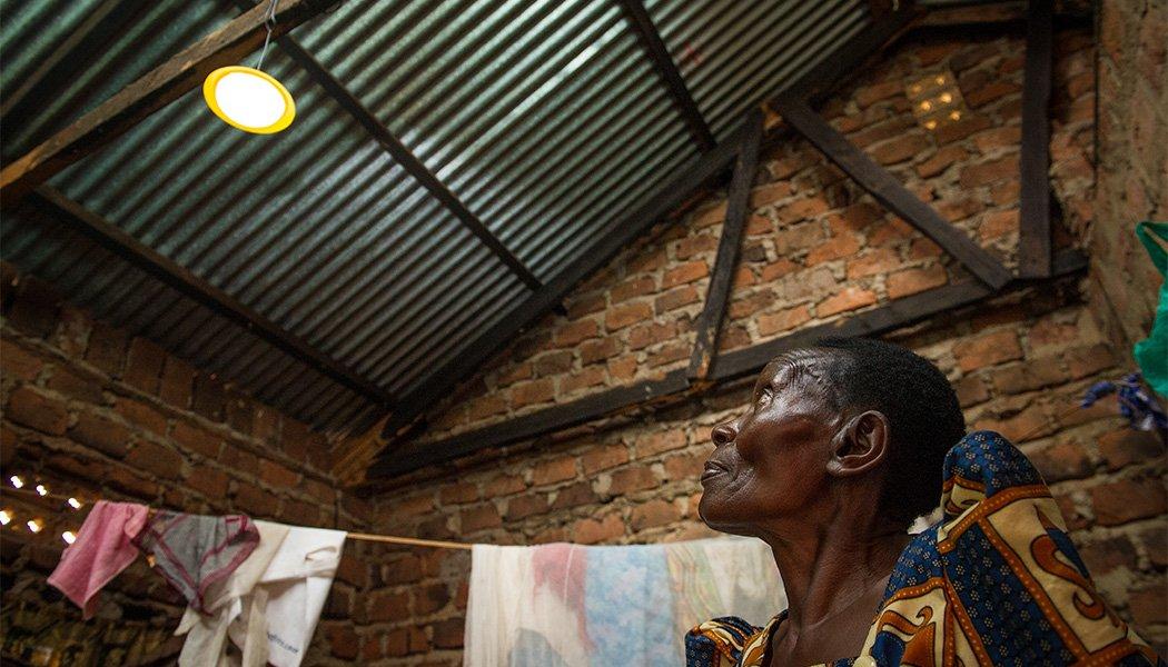 BrightLife Client Margaret Nankonge Looking at her Solar Home System