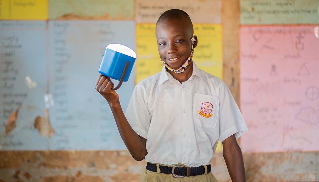 A Boy Smiles as His Picture Is Taken with a New Solar Lantern