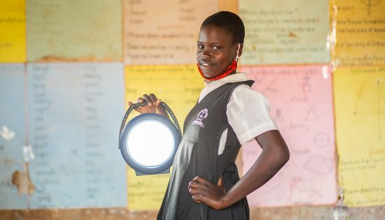 Student posing with a solar lamp