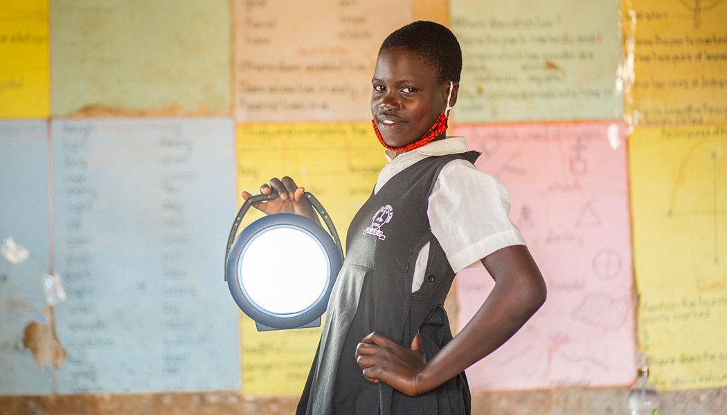A Female Student Stands with a Solar Lamp