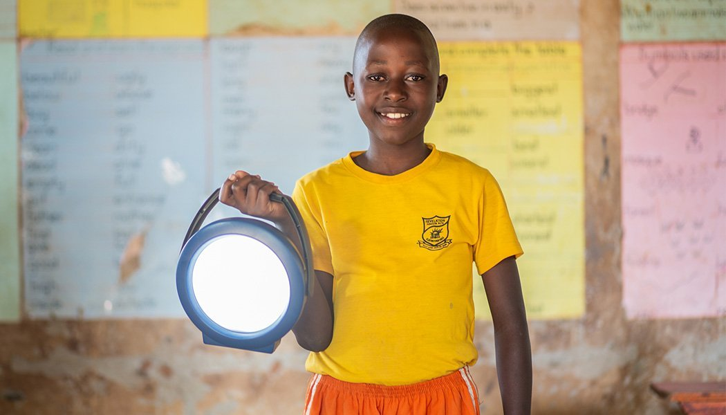 A Student Smiles Holding a New Solar Lantern