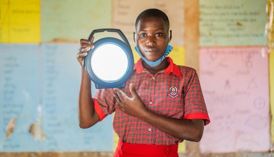 A Student Stands Holds a Lamp from the New Solar Lamp Library