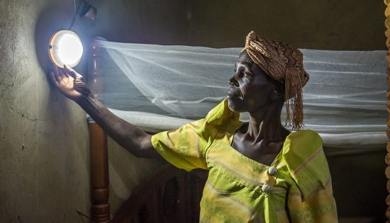 A BrightLife client adjusts the solar light on her solar home system.