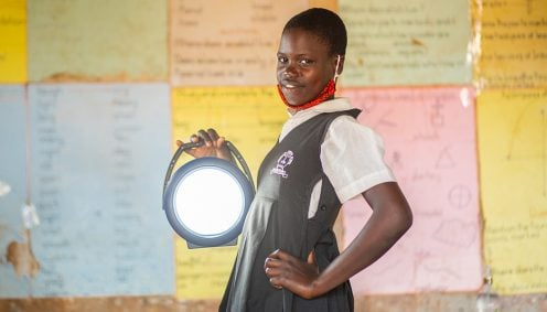 A girl holding a solar lamp provides an example of how even as the COVID crisis in Africa grows, BrightLife uses sustainable solar lighting to empower women and girls.